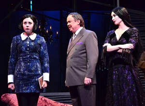 Gomez Addams (Eddie Curry, center) is caught between honoring the wishes of his daughter Wednesday (Samantha Russell, left) and wife Morticia (Erin Cohenour) in a scene from